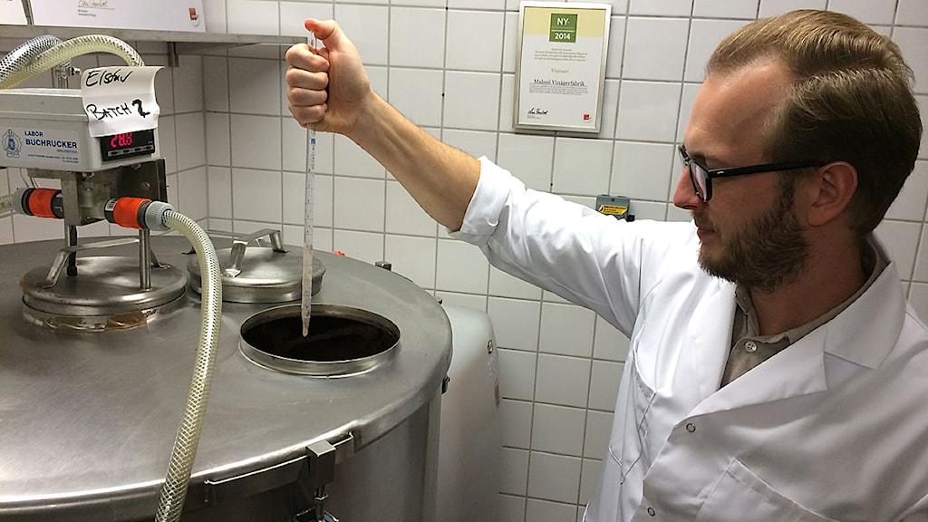 Andreas Larsson mäter syran i vinägern. Foto: Madeleine Fritsch-Lärka/Sveriges Radio