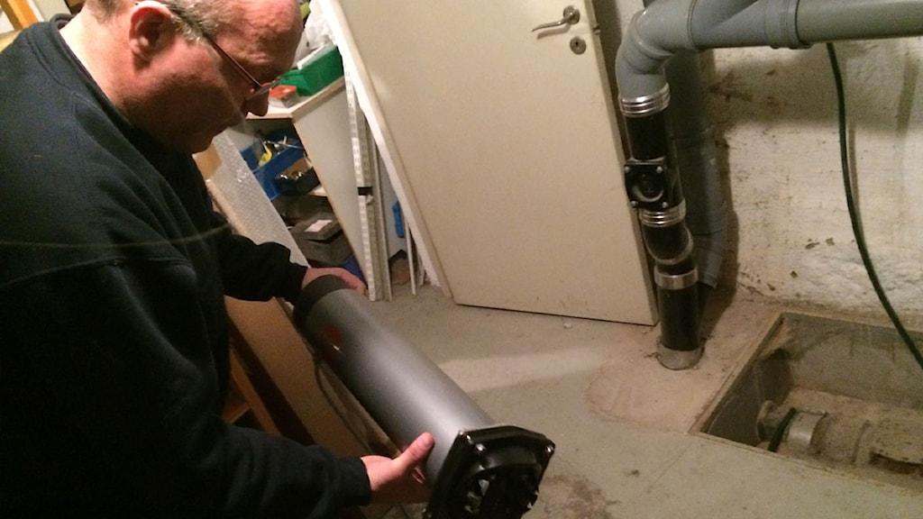 Ola Severin från Anticimex i färd med att installera en wise-pipe som ska fånga råttorna. Foto: Anton Kalm / Sveriges Radio