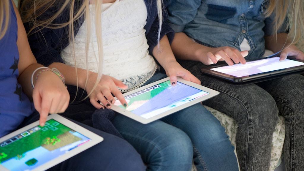 Tre kompisar spelar datorspelet Minecraft online på sina surfplattor. Foto: Fredrik Sandberg / TT