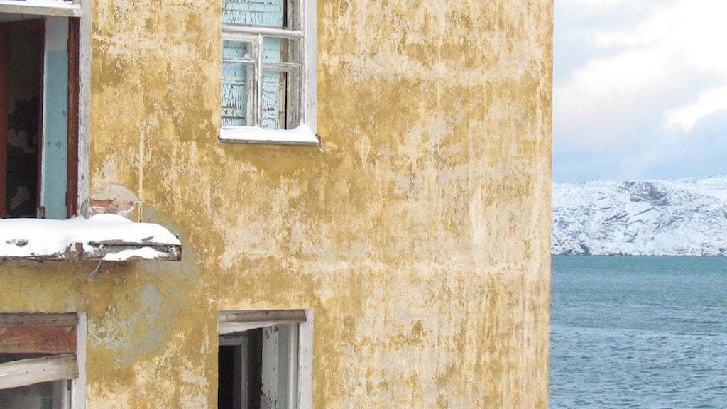 Naturgasen i Barents hav ska förvandla Teriberka till ett paradis. Närbild på husvägg med havet i bakgrunden. Foto: Eva Elke Sveriges Radio